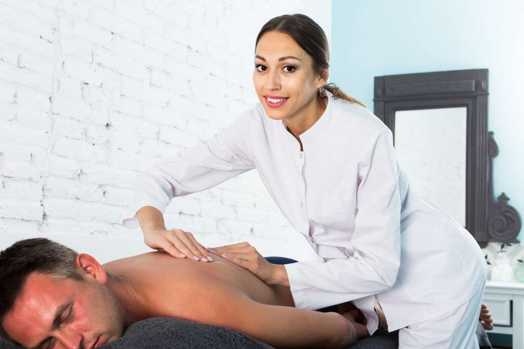 A Massage Therapist Working on Her Patient
