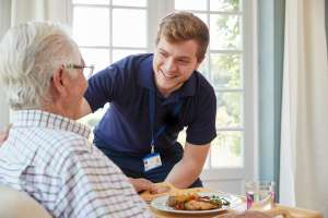 Personal Support Worker serving dinner and speaking