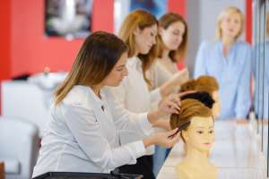Instructor watches over her hairstyling class